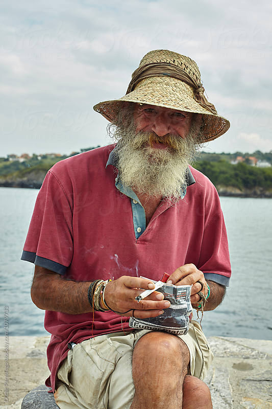 Bohemian Man smoking in the harbour by Oscar Parasiego for Stocksy United