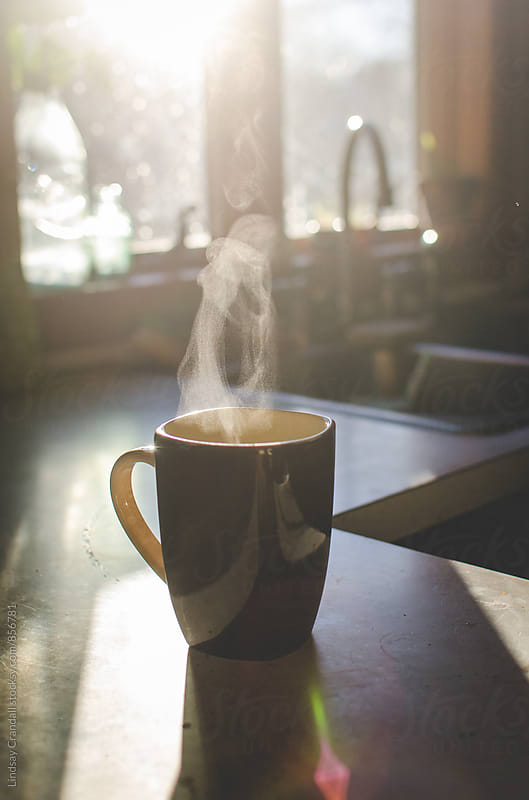 Steaming cup of coffee in sunlit kitchen by Lindsay Crandall for Stocksy United