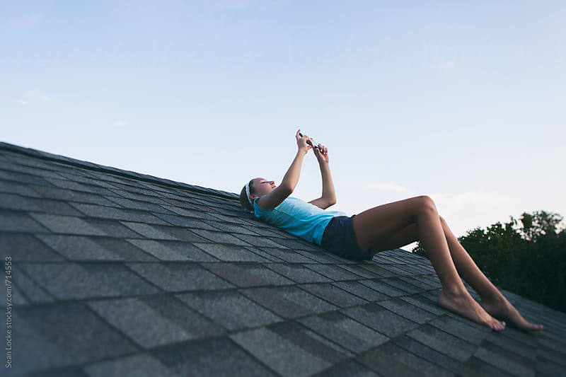 Roof: Teen Girl Uses Cell Phone On The Rooftop Of A House by Sean Locke for Stocksy United