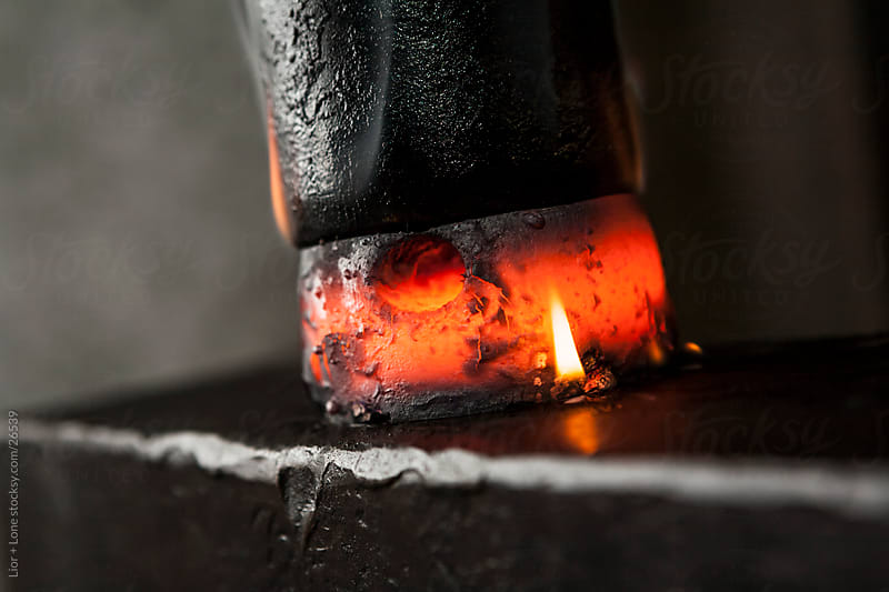 Hot metal crushed between hammer and anvil by Lior + Lone for Stocksy United