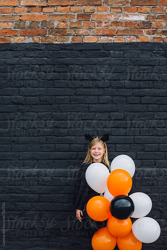 Cute Halloween Witch Holding Balloons by Lumina for Stocksy United