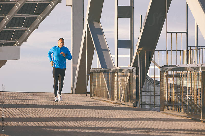Man running on a urban bridge. by BONNINSTUDIO for Stocksy United