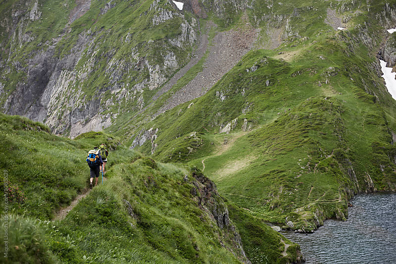 Backpackers in a trail of the Pyrenees by Miquel Llonch for Stocksy United