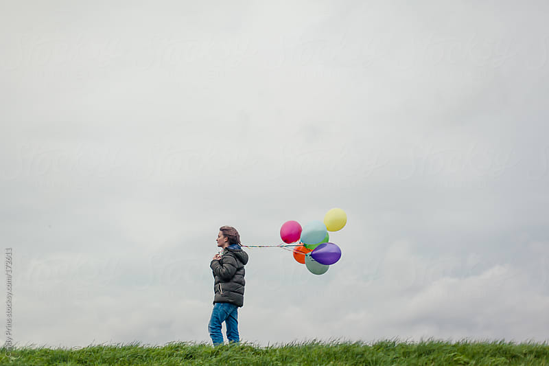 Boy walking against a cloudy sky holding a bunch of balloons by Cindy Prins for Stocksy United