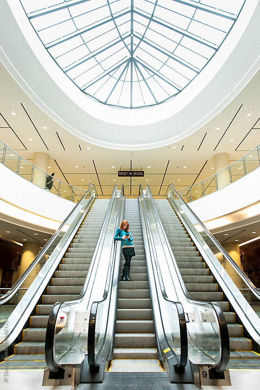 Business Woman Alone In Large Office Tower Atrium With Cell Phone by JP Danko for Stocksy United