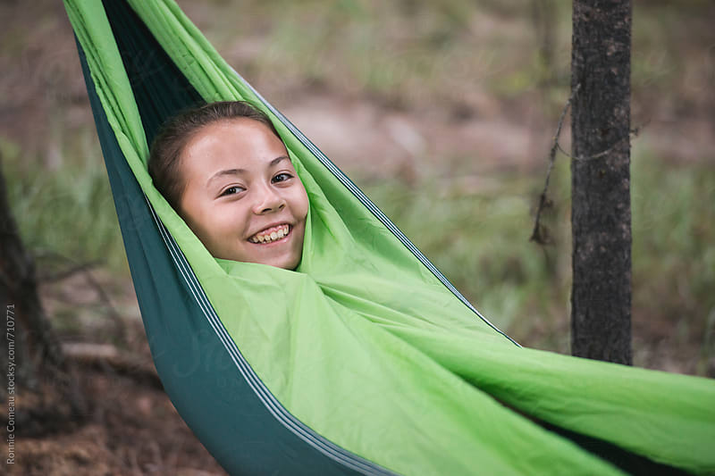 Young Girl In Hammock In Woods by Ronnie Comeau for Stocksy United