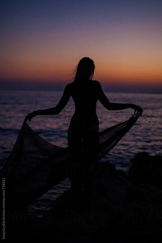 Shadow of a fit girl in the sunset holding a pareo by Sanja (Lydia) Kulusic for Stocksy United