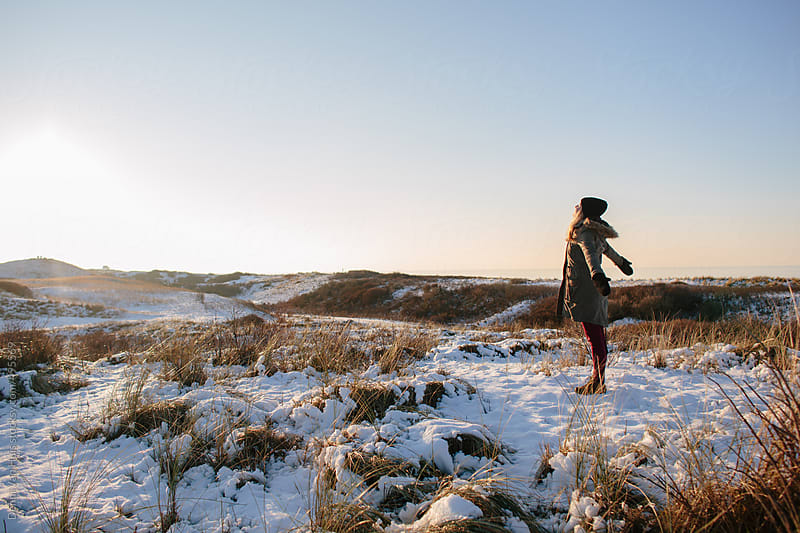 A woman standing in a snowy field looking at the sun. by Denni Van Huis for Stocksy United