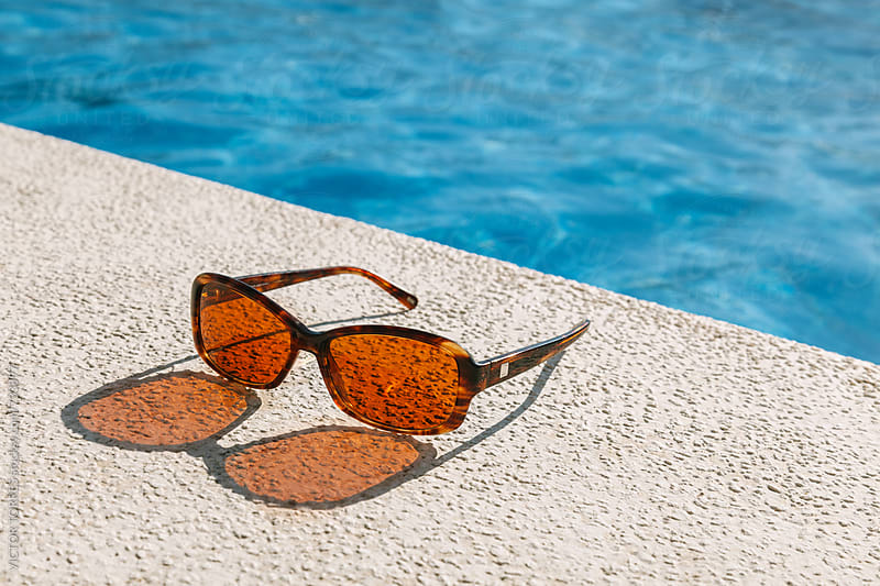 Brown Sunglasses by the Pool by Victor Torres for Stocksy United