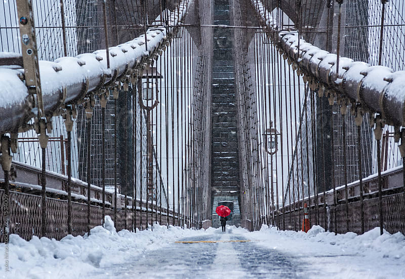 Tourist standing on Brooklyn Bridge in snow, New York by yuko hirao for Stocksy United