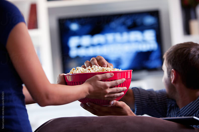 Television: Couple Having Popcorn and Watching Movie by Sean Locke for Stocksy United