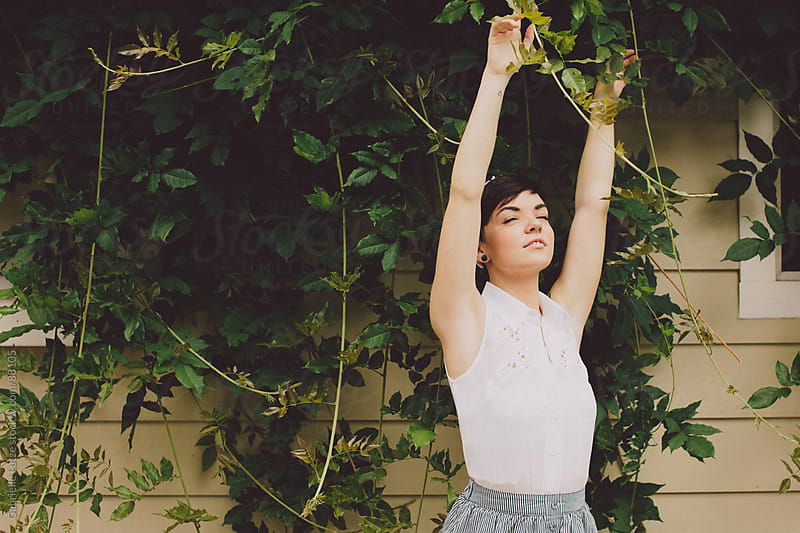 Girl with short hair reaching arms up in front of vines by Gabrielle Lutze for Stocksy United