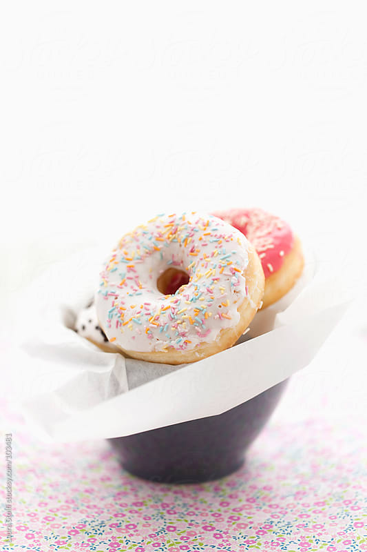 Colourful doughnuts with sugary on them pile in a cup on flowered cotton cloth  by Laura Stolfi for Stocksy United