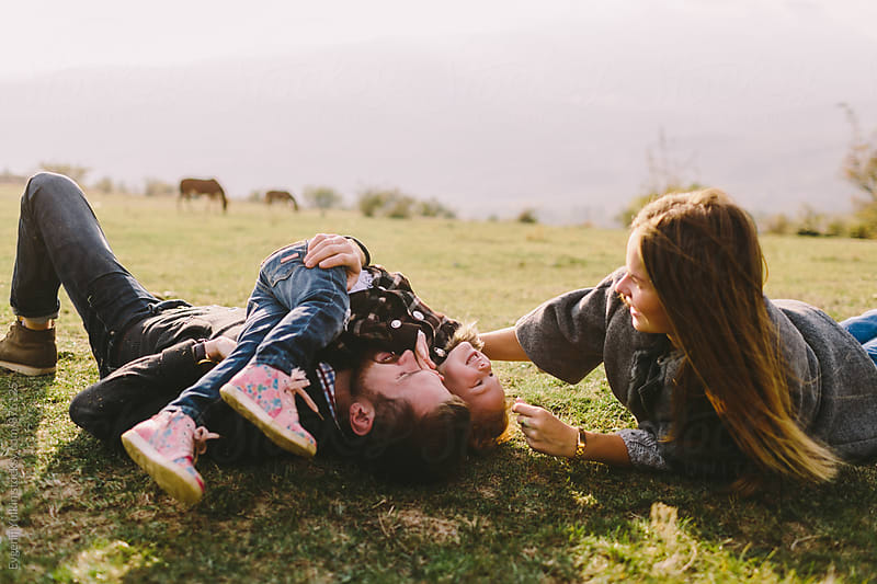Family laying on the grass and have fun by Evgenij Yulkin for Stocksy United