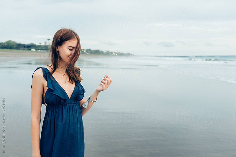 Young Brunette Woman Enjoying Wind at the Beach by Nemanja Glumac for Stocksy United