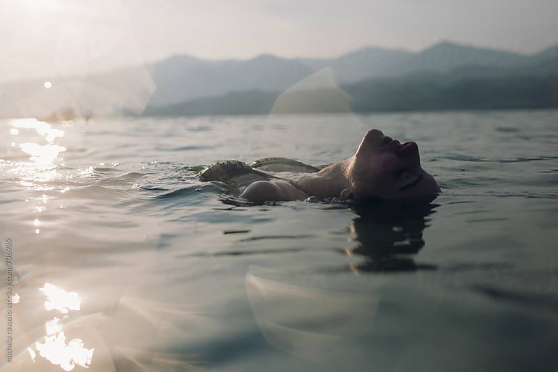 Young woman floating in lake at sunset by michela ravasio for Stocksy United