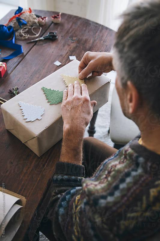 Elderly man decorating the Christmas present by Danil Nevsky for Stocksy United