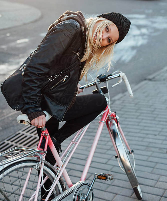 Pretty blonde smiling woman posing on the street with bicycle by Viktor Solomin for Stocksy United