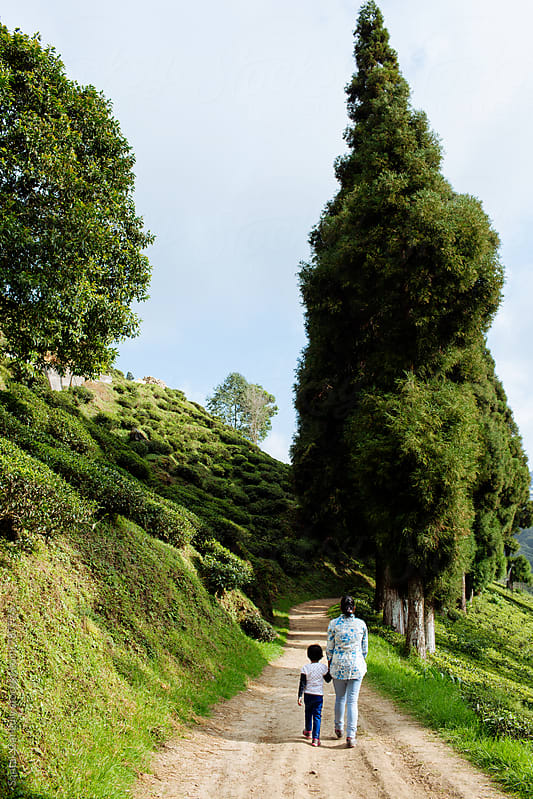 Woman walking on a hilly path with her daughter,back view by Saptak Ganguly for Stocksy United