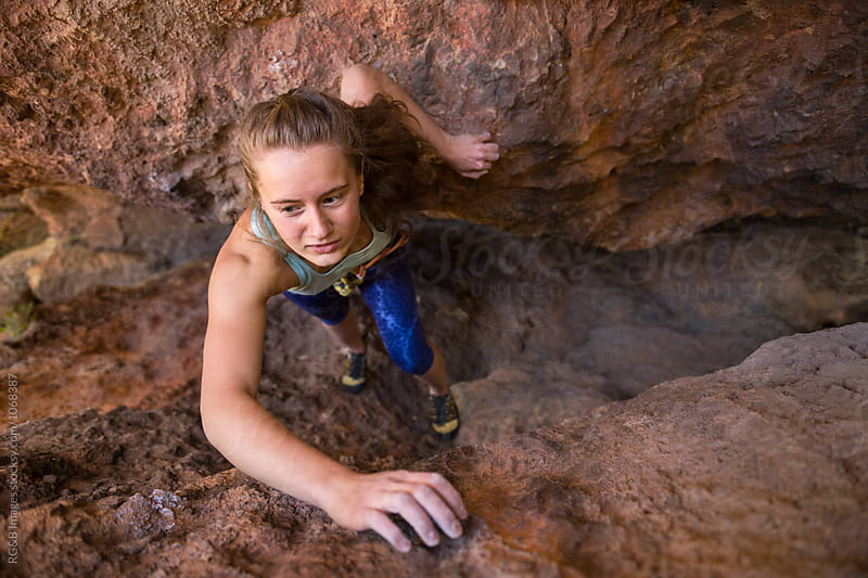 Female climber rock climbing through a narrow chimney by RG&B Images for Stocksy United