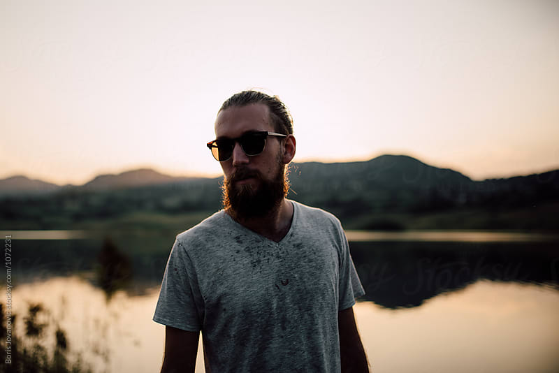 Portrait of bearded man with glasses standing in front of the mountain lake by Boris Jovanovic for Stocksy United