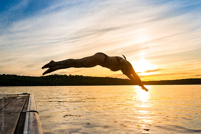 Woman Diving Off Dock Into Warm Summer Cottage Lake At Sunset by JP Danko for Stocksy United