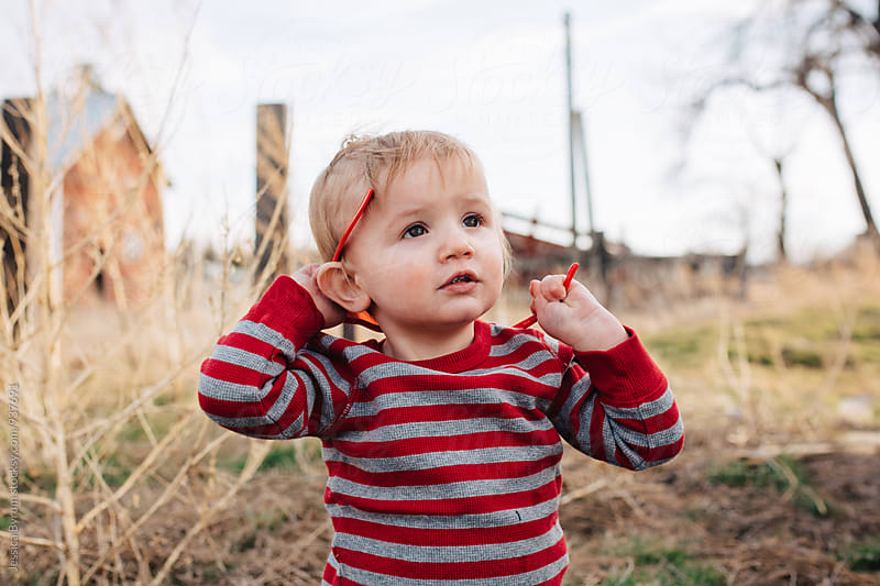 Toddler boy playing with sunglasses by Jessica Byrum for Stocksy United