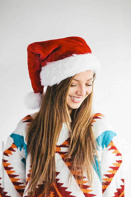 Portrait of a cheerful woman with christmas hat by Aleksandar Novoselski for Stocksy United