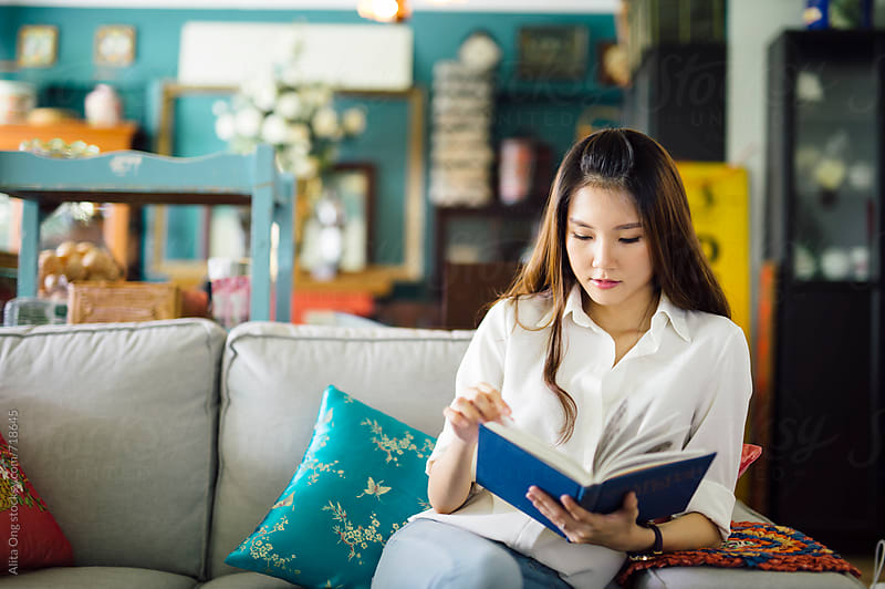 Beautiful woman reading in living room at home by Alita Ong for Stocksy United