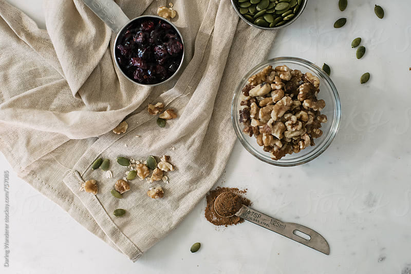 Homemade grandola nuts and oats ingredients in measuring cups on marble table by Daring Wanderer for Stocksy United