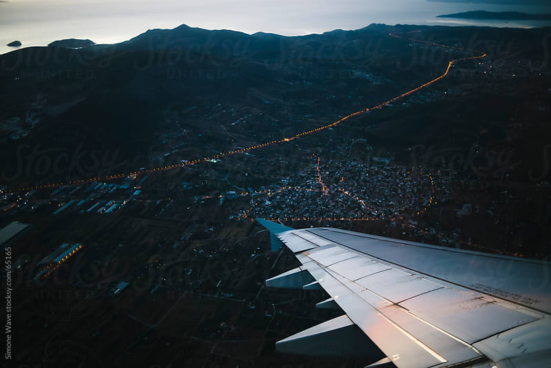 Airplane flying above a city during twilight by GIC for Stocksy United