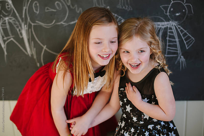 Two young girls dressed up in their holiday best hold hands laughing. by Kelsey Gerhard for Stocksy United