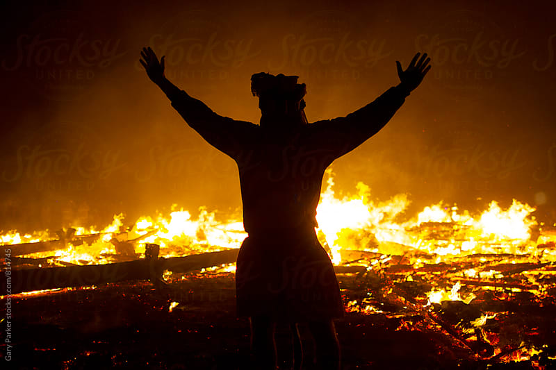A black silhouette of a man in front of a large fire. by Gary Parker for Stocksy United