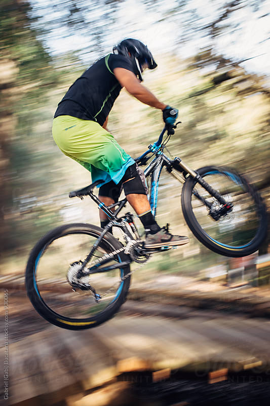 Mountain bike rider jumps on a hill by Gabriel (Gabi) Bucataru for Stocksy United