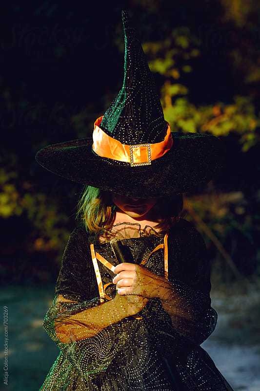 Young girl in witch costume in woods by Alicja Colon for Stocksy United