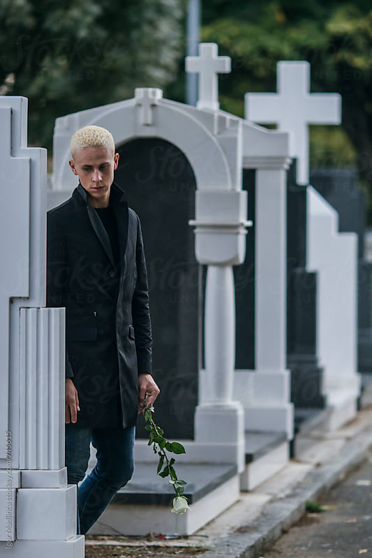 blond young man with white rose dressed in black on the graveyard by Igor Madjinca for Stocksy United