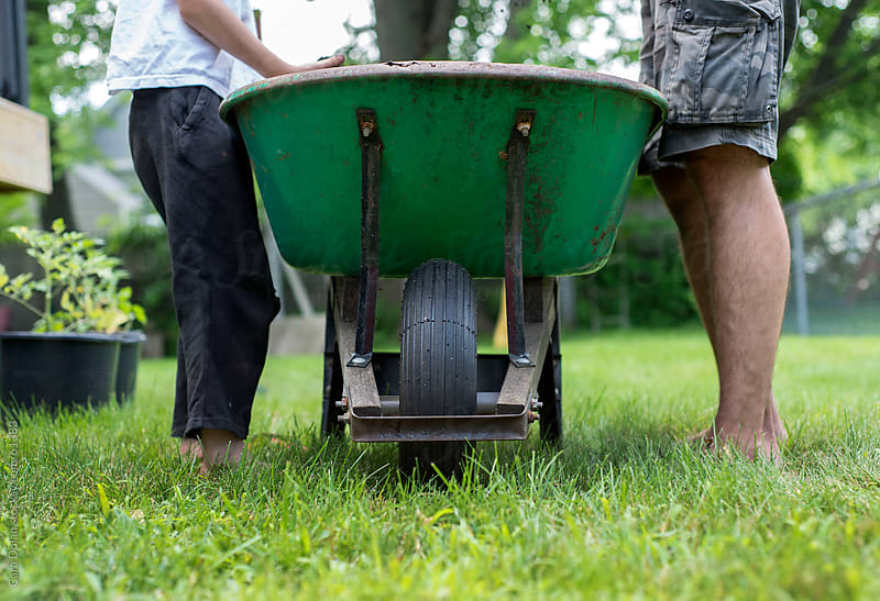 Father and son stand on either side of a wheelbarrow by Cara Dolan for Stocksy United