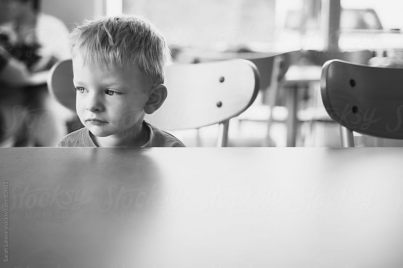 a little boy sitting at an empty table looking grumpy by Sarah Lalone for Stocksy United