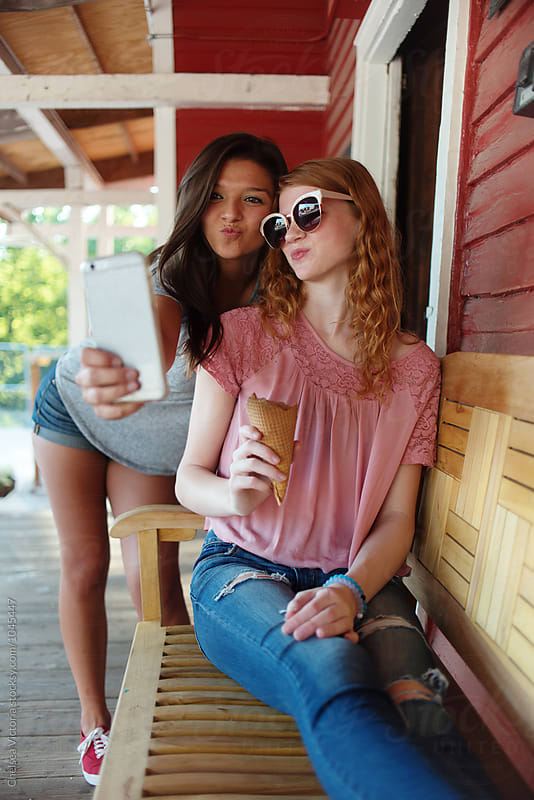 Teenage sisters sharing ice cream and taking selfies by Chelsea Victoria for Stocksy United
