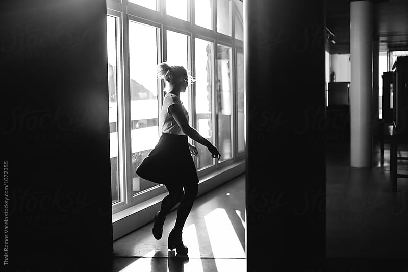 Girl dancing in front of a window  by Thais Ramos Varela for Stocksy United