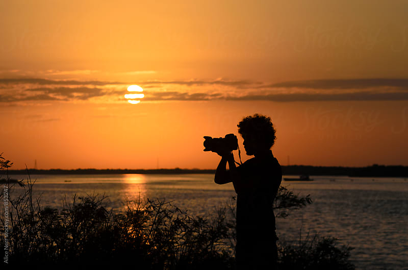 Black silhouette of photographer with his camera nearby lake at sunrise by Alice Nerr for Stocksy United