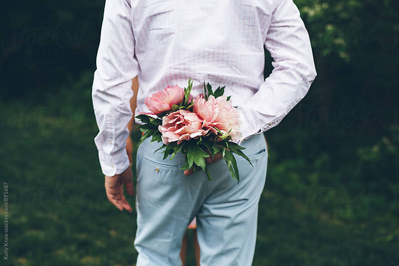man holding a peony bouquet behind his back  by Kelly Knox for Stocksy United