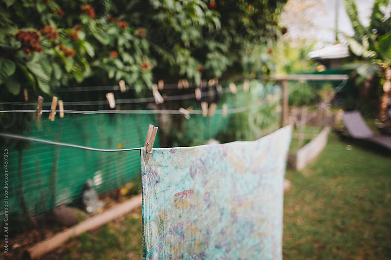 floral sheet hanging on clothesline in yard by Rob and Julia Campbell for Stocksy United