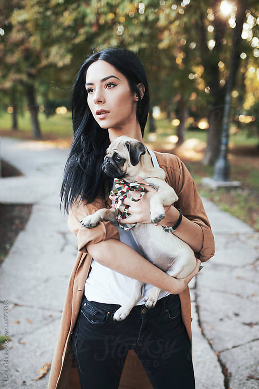 Fashionable young woman and a pug dog by Jovana Rikalo for Stocksy United