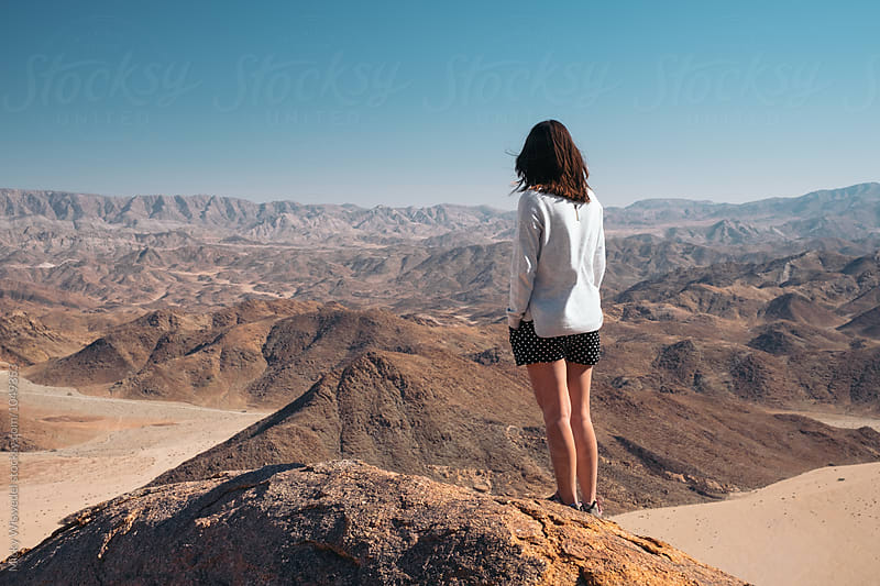 woman on a mountain summit overlooking a scenic desert view by Micky Wiswedel for Stocksy United