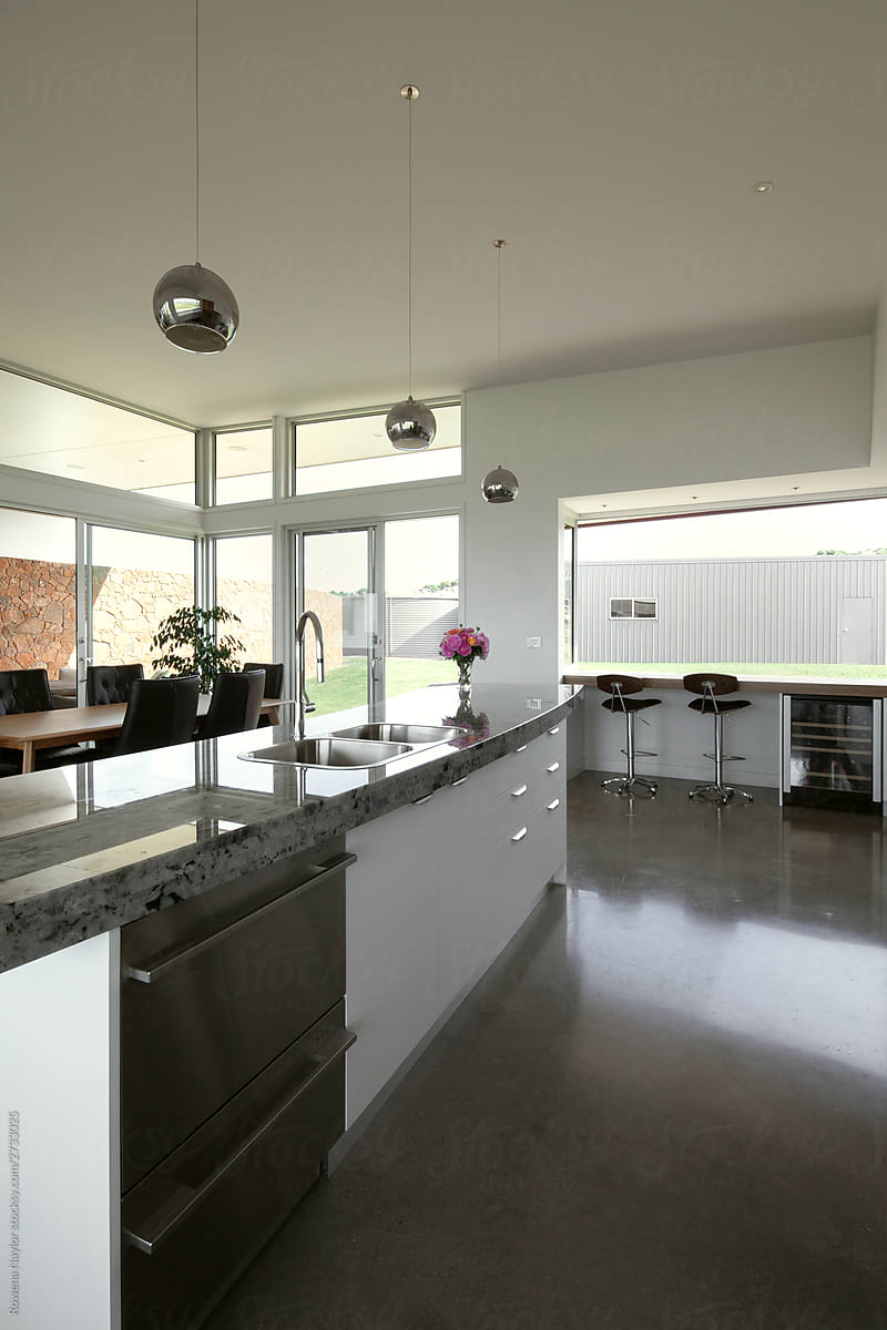 Modern Kitchen With Curved Island Bench And Chrome Pendant Lights Por Rowena Naylor Stocksy United