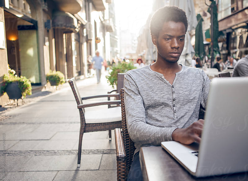 Young African Using Laptop at a Cafe by Lumina for Stocksy United