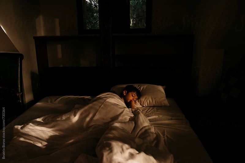 Boy sleeping in his bed at home by Beatrix Boros for Stocksy United