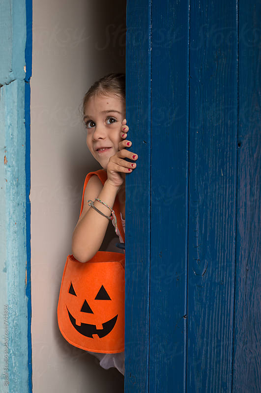 Little ballerina behind a blue door with a halloween bag by Bisual Studio for Stocksy United