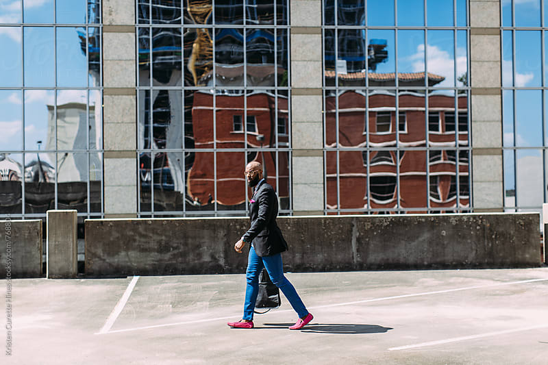 An African American man walking in business attire outdoors in the city by Kristen Curette Hines for Stocksy United